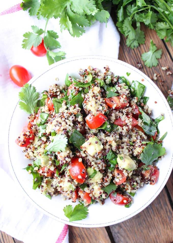 Superfoods quinoa salad with avocado, spinach and tomatos. Tossed in a ...