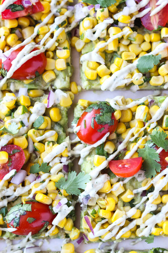 Thin crust flatbread with guacamole, corn, tomatoes, and drizzle of avocado cream. SUPER easy light lunch or meatless dinner | LittleBroken.com @littlebroken