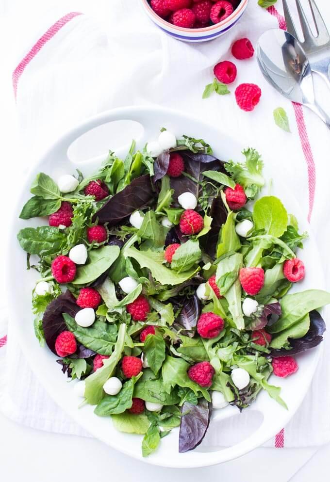 Fresh raspberries, mozzarella balls, basil, and greens. Tossed in the most delicious homemade raspberry vinaigrette | littlebroken.com @littlebroken