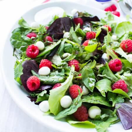 Fresh raspberries, mozzarella balls, basil, and greens. Tossed in the most delicious homemade raspberry vinaigrette | littlebroken.com @littlebroken
