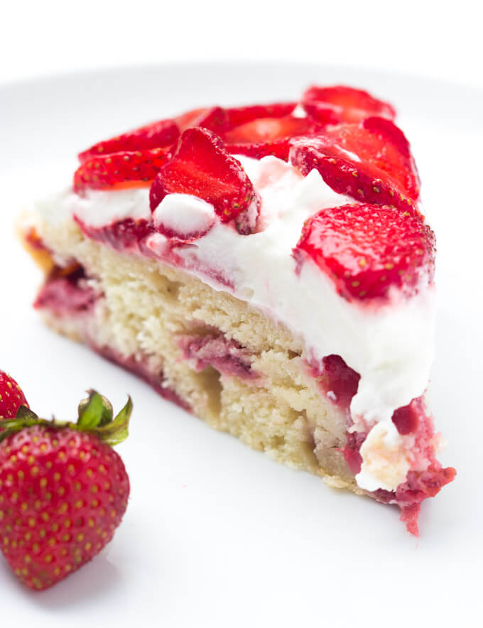 Single slice strawberry shortcake cake on white plate
