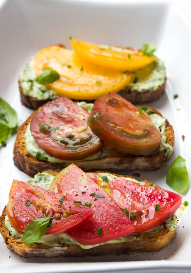 Crisp toast topped with garlic-herb mayonnaise and sweet juicy heirloom tomato slices. Breakfast, lunch, or dinner at its finest | littlebroken.com @littlebroken