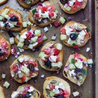 Easy, all from scratch appetizer that is loved by everyone! Zesty greek salad a top of a golden crisp crostini | littlebroken.com @littlebroken