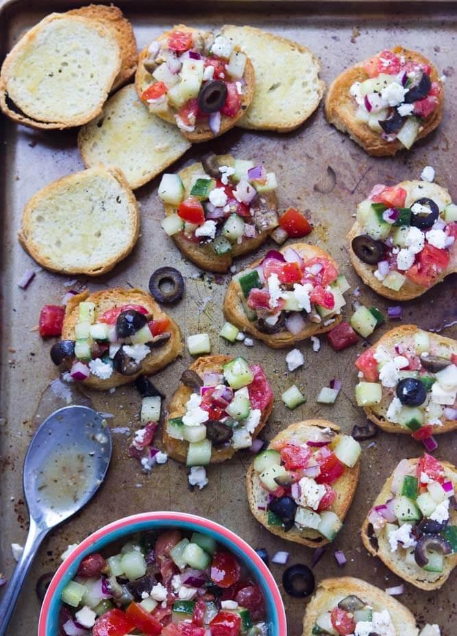 Easy, all from scratch appetizer that is loved by everyone! Zesty greek salad a top of a golden crisp crostini | littlebroken.com @littlebroken