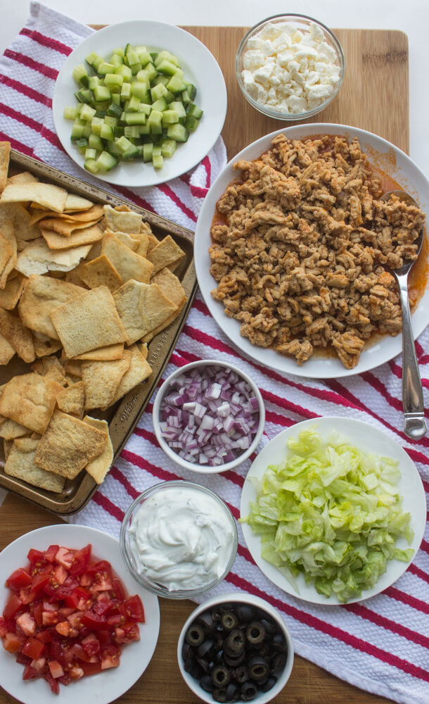 Mediterranean Nachos - ultimate game day appetizer! Layers of seasoned meat, fresh veggies, feta, and homemade tzatziki sauce a top of crispy pita chips | littlebroken.com @littlebroken