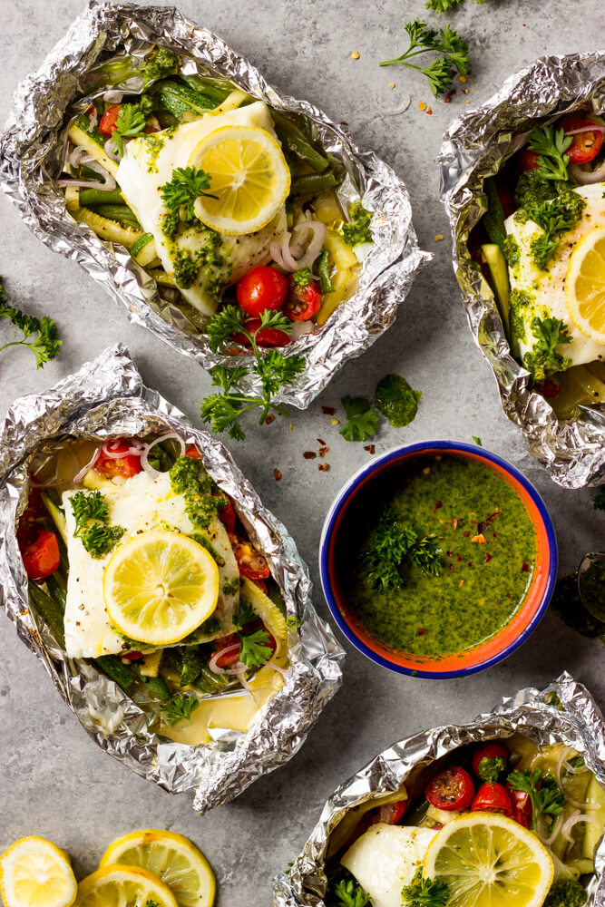 baked fish with vegetables in foil with chimichurri sauce