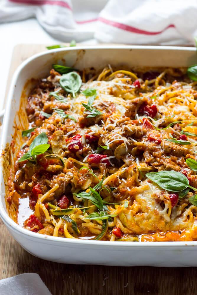 Side close-up of spaghetti zucchini bake in white casserole dish