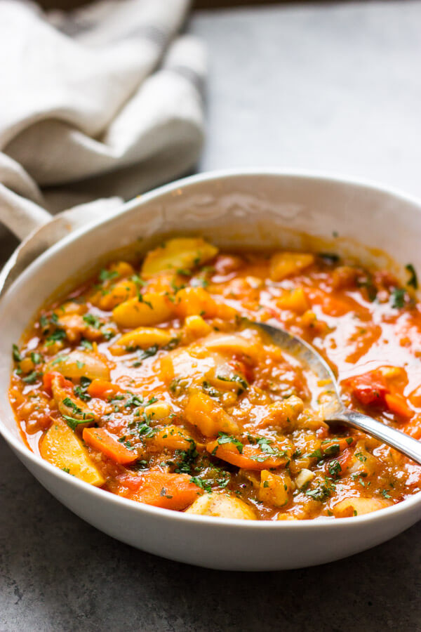 Side view of chicken stew with butternut squash in white bowl
