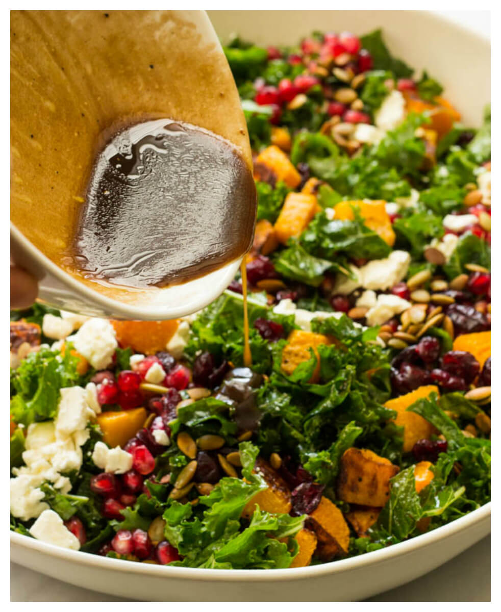 Close up of kale salad with dressing being poured