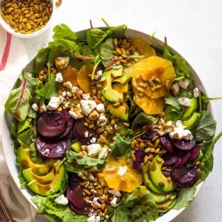 Overhead of roasted beet salad with avocado in white bowl
