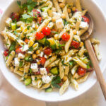 Cold pasta salad with italian dressing in white bowl and wooden spoon
