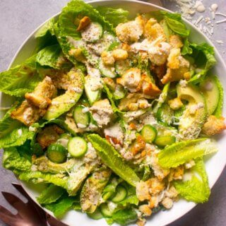 Overhead avocado caesar salad in white salad bowl