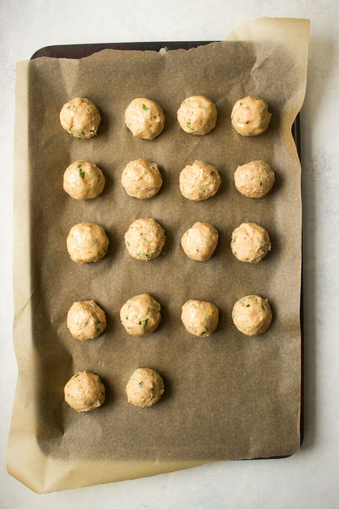 Raw chicken meatballs on parchment lined baking sheet