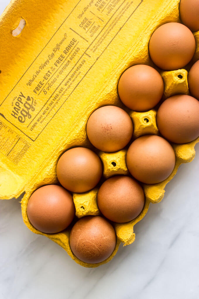 Overhead brown eggs in yellow egg carton