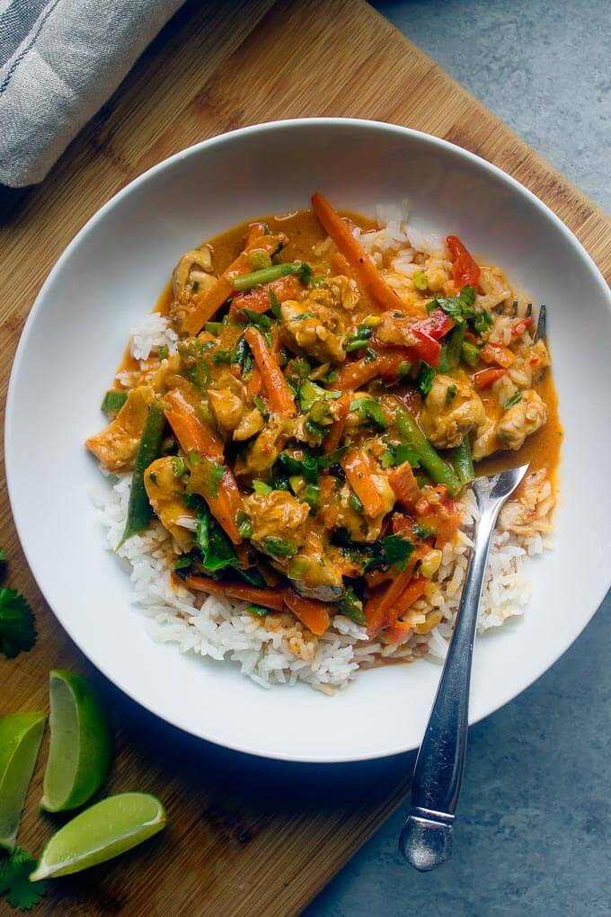 Chicken vegetable curry over white rice in white bowl with side of fork
