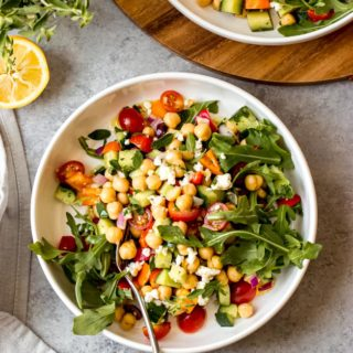 Overhead greek chickpea salad in white bowl on gray background