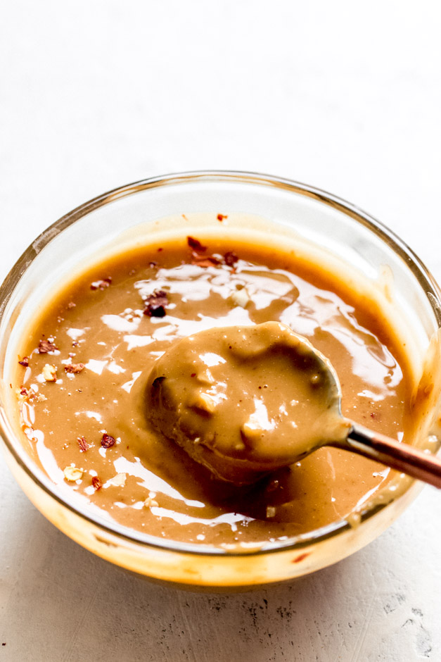Close up of peanut sauce in glass bowl with spoon