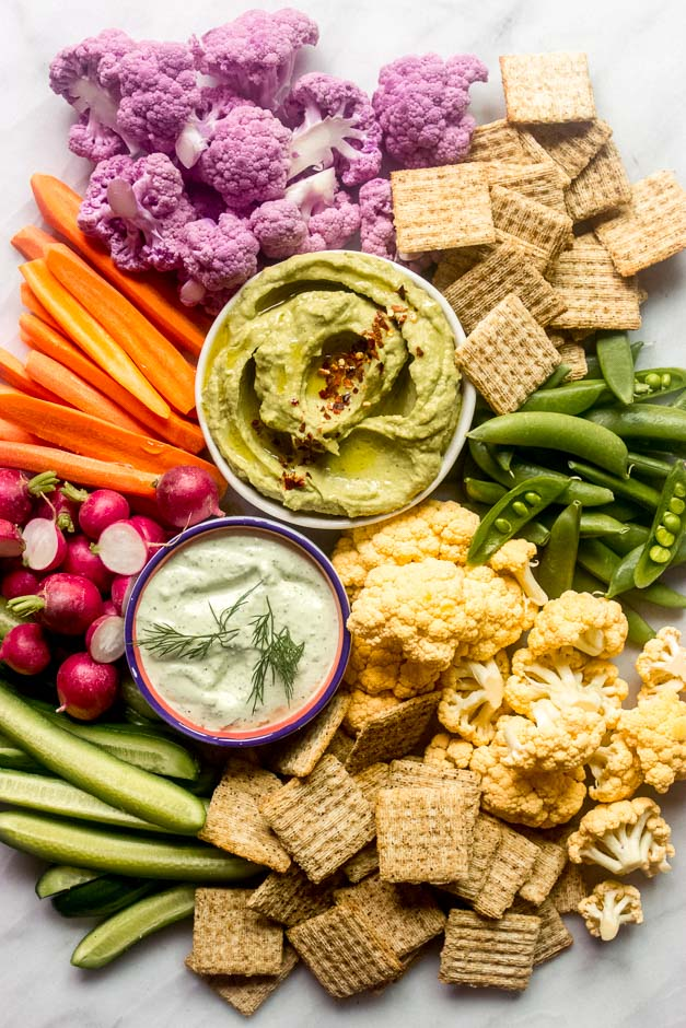 Overhead crudite platter with vegetable dips in the middle