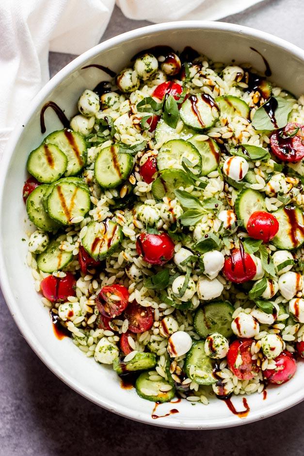 Overhead caprese orzo salad in white bowl