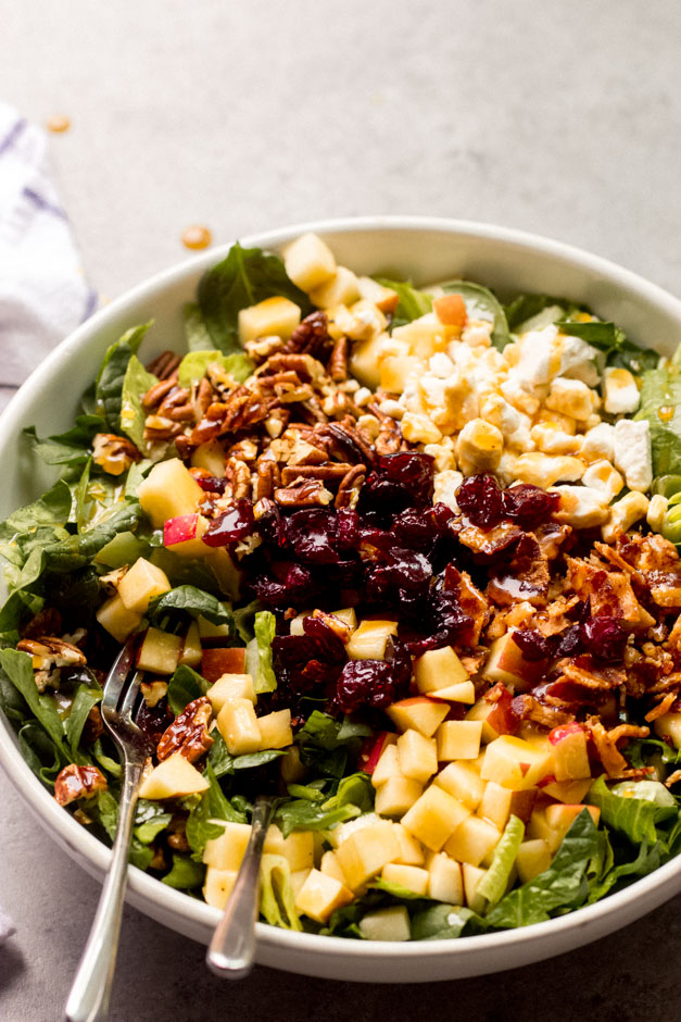 spinach and apple salad in white bowl
