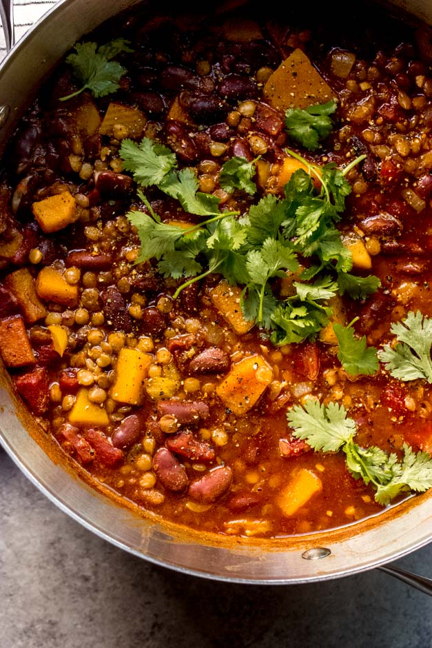 close up butternut squash and lentils chili in soup pot